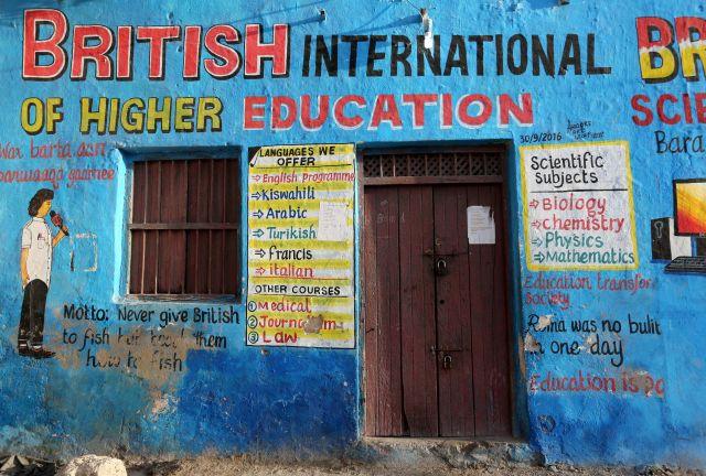Một bức tranh tường bằng tiếng Anh giới thiệu các lớp học bên ngoài một tòa nhà ở quận Mogadishu, Somali.