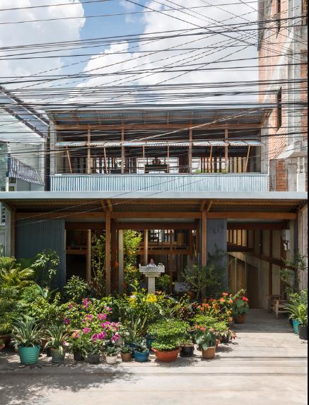 Lối vào nhà được thiết kế đơn giản, dọc hai bên là những chậu cây hoa đẹp.