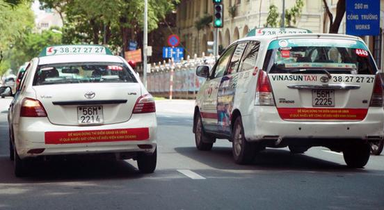 Hai chiếc taxi Vinasun mang biểu ngữ Đề nghị dừng thí điểm Grab và Uber vì quá nhiều bất công về điều kiện kinh doanh - Ảnh: THUẬN THẮNG