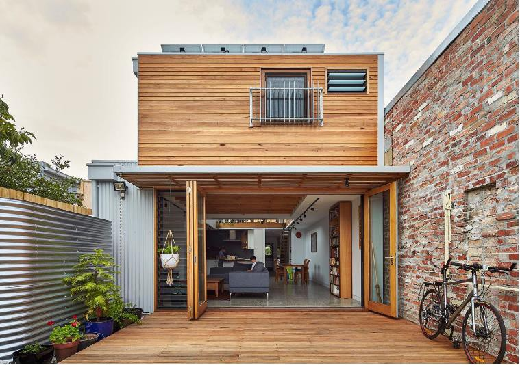 Ngôi nhà ống xinh xắn được xây dựng trên diện tích 180m2 với phần trước nhà được thiết kế 2 tầng. Không gian tầng 1 được thiết kế với phòng khách, bếp và hai phòng ngủ sâu bên trong. Ngay trước nhà là cả một khoảng không rộng thoáng được ốp gỗ sạch sẽ.