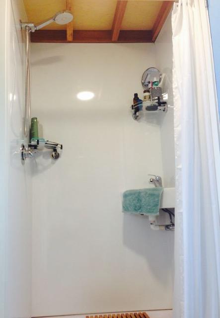 Khu vực tắm đứng được phân biệt bằng một chiếc rèm trắng dày.