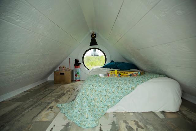 Một phòng ngủ đơn giản với chiếc gương tròn lớn tuyệt đẹp.