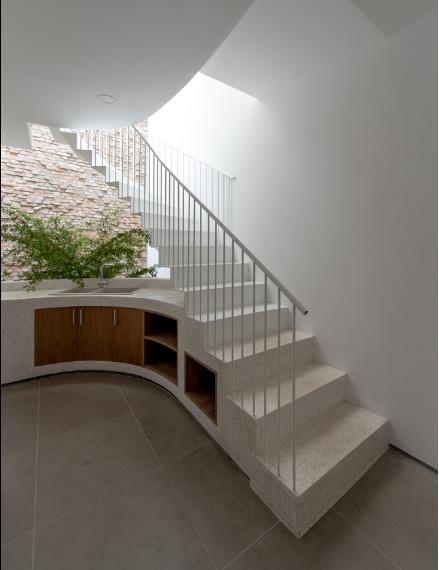 Cầu thang được ốp đá cùng tông với kệ bếp, khu vực bồn rửa tạo sự nhất quán trong thiết kế.