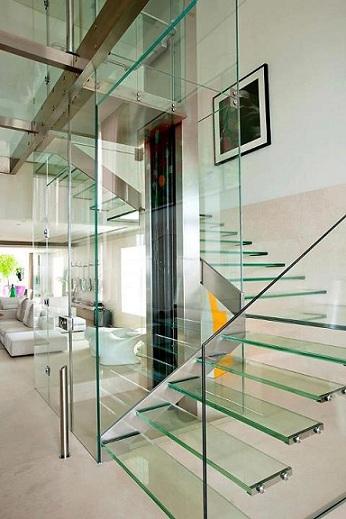Các không gian chức năng trong nhà không còn bị ngăn cách nhờ chiếc cầu thang kính trong suốt.