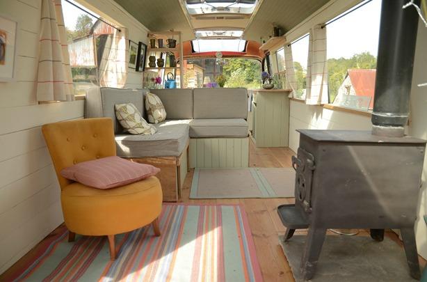 Khu vực tiếp khách được bày trí đơn giản, thanh lịch với bộ sofa góc, thảm trải sàn gam màu trung tính, không quên những giỏ hoa rực rỡ một góc phòng.