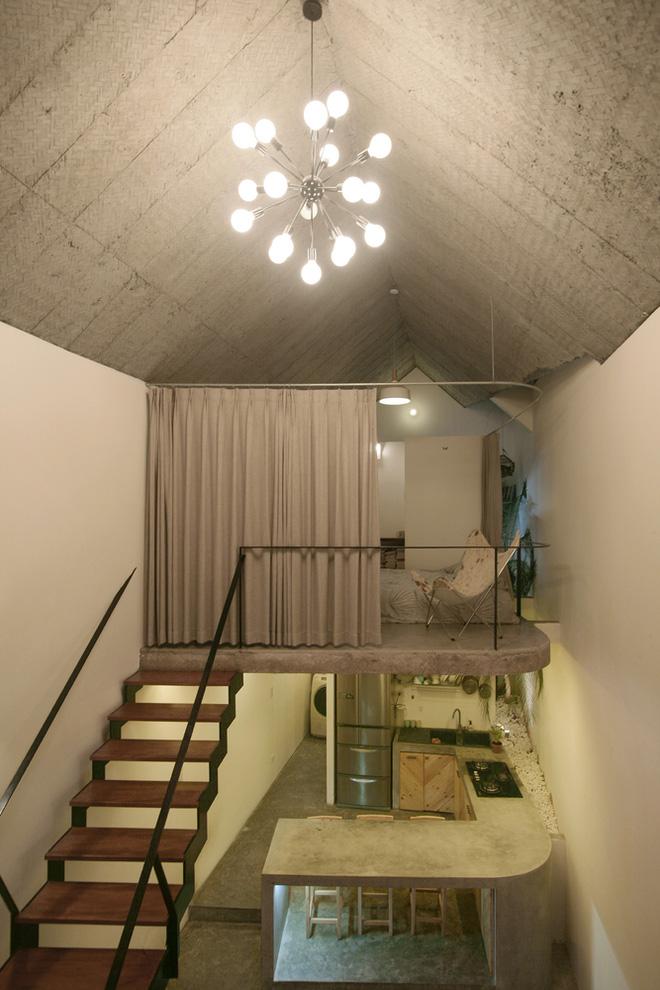 Tầng lửng được thiết kế làm bằng bê tông trần, với góc cong tương ứng với bàn bếp bên dưới, tạo nên vẻ đẹp đồng điệu và thông thoáng cho cả ngôi nhà.