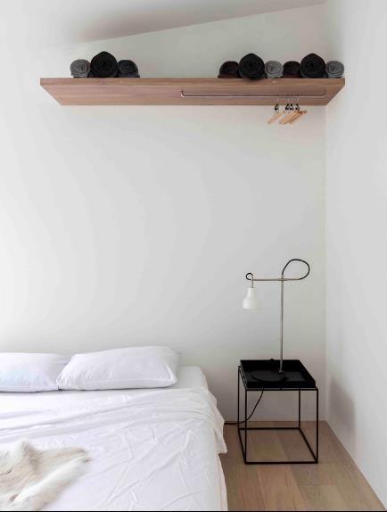 Không sử dụng tủ quần áo như bình thường mà chủ nhà chọn kệ gỗ kết hợp móc treo đồ trên cao để tạo không gian thoáng sáng cho góc nghỉ ngơi.
