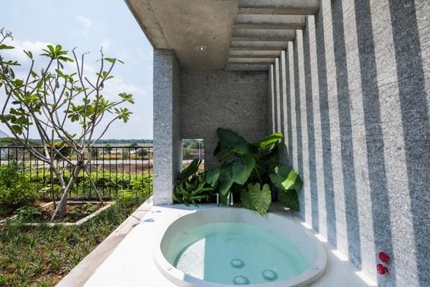 Một bồn tắm thoáng mát cạnh khu vườn đầy cây xanh.