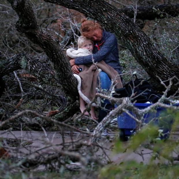 Chị Lias Rehr ôm con trai 4 tuổi Maximus trong khi đang đợi lực lượng cứu hộ giải cứu. Căn nhà của họ tại Rockport đã bị hư hỏng hoàn toàn.