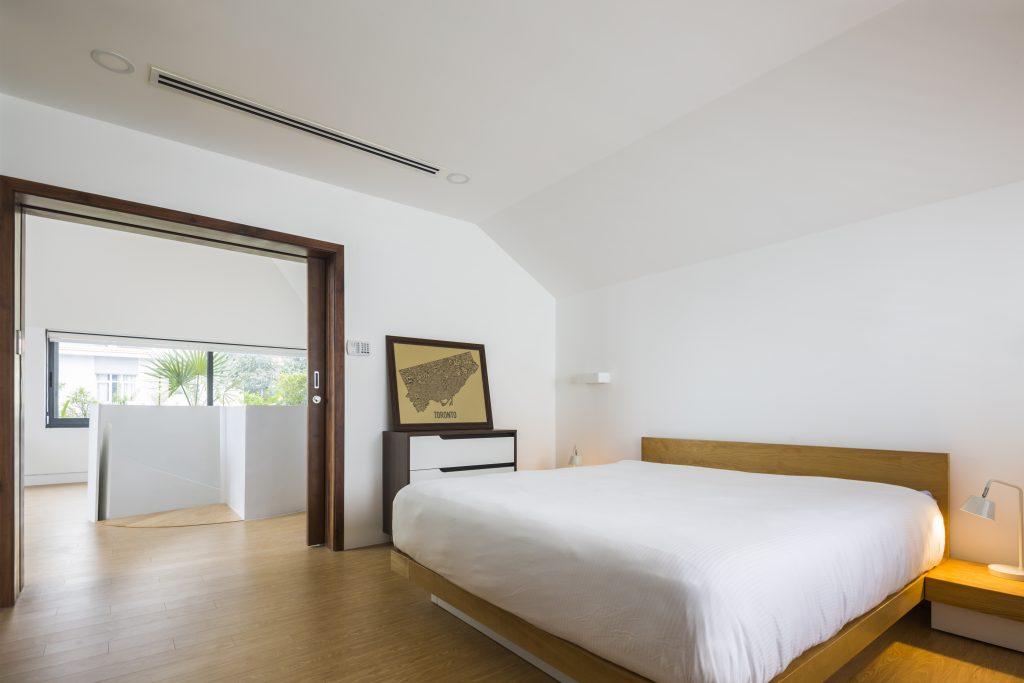 Phòng ngủ được thiết kế đơn giản, thoáng mát với tông màu trắng chủ đạo.