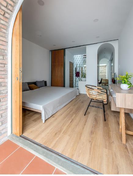 Không gian phòng ngủ lớn được ốp sàn gỗ sáng màu.