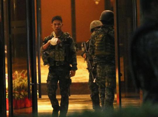 Một cảnh sát bị thương đứng tại cửa khu phức hợp Resorts World Manila sau khi nổ súng xảy ra. Ảnh: Reuters