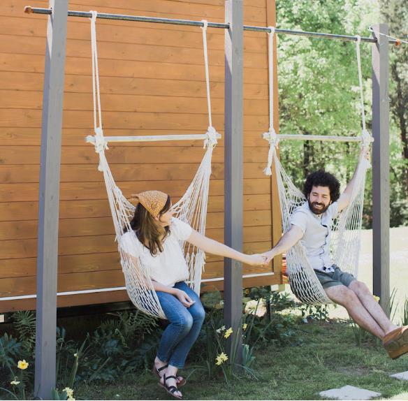 Không gian trước nhà được hai vợ chồng khéo léo trồng hoa và bố trí hai chiếc xích đu làm không gian thư giãn ngoài trời vô cùng lãng mạn.