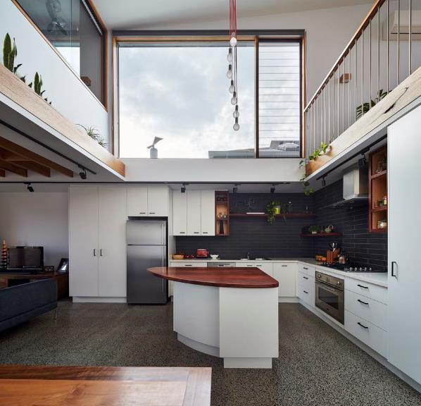 Bếp và phòng khách được đặt trong cùng một không gian mở rộng thoáng. Góc nấu ăn được dành riêng một góc thoáng sáng nhờ một bức tường kính lớn và thông thằng giữa tầng 1 và tầng 2.