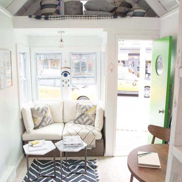 Góc tiếp khách được đặt ngay cạnh cửa ra vào với chiếc ghế hình chữ nhật kê sát tường cùng hai bàn trà nhỏ xinh bên cạnh.