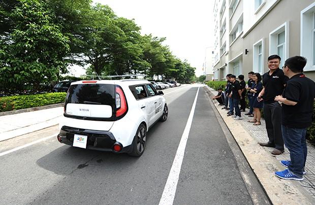 Lãnh đạo FGA cùng nhóm R&D đứng trên vỉa hè quan sát và trao đổi trong khi một số nhân sự đang thử xe.