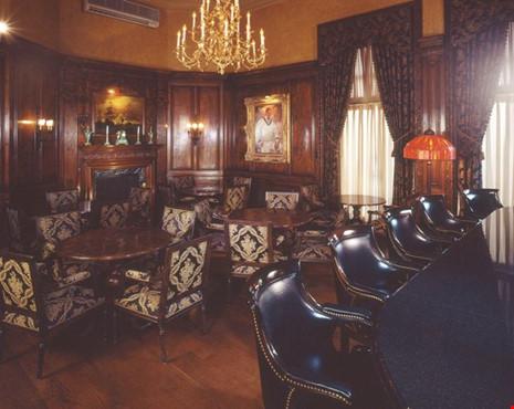Căn phòng ở biệt thự có tường và sàn được ốp bằng gỗ gụ, với những chiếc ghế được làm theo kiểu cách kỳ lạ.