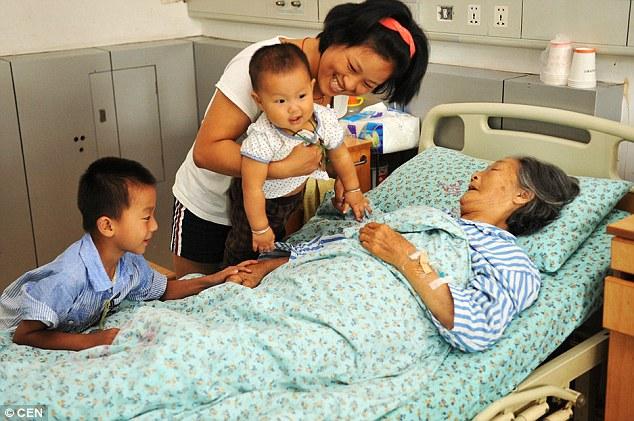 Người con gái lớn và 2 trong số những đứa bé bà nhặt về đến thăm bà tại bệnh viện (Ảnh: Internet).