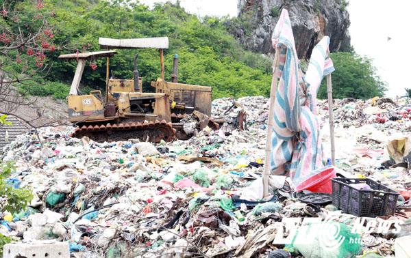 Chiếc máy ủi dùng để chôn lấp rác nằm đắp chiếu ở một góc bãi rác.