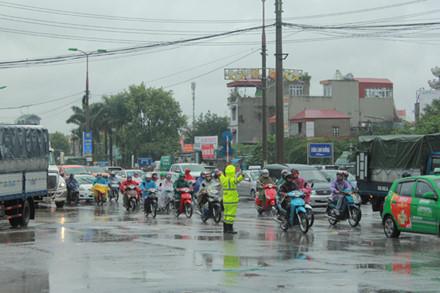 Dù thời tiết mưa rét, lực lượng Cảnh sát giao thông vẫn phải căng mình điều tiết, phân luồng giao thông để hạn chế tối đa tình trạng ùn tắc kéo dài.