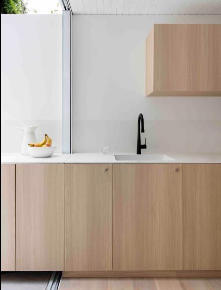 Khu vực nấu ăn được thiết kế đơn giản và tiện dụng với hệ tủ kệ gỗ kéo dài đến hết khu vườn.