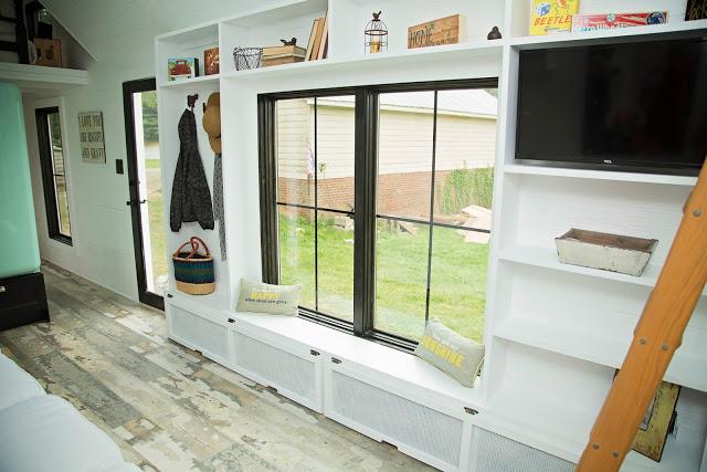 Dọc hai bên tường được thiết kế với hệ thống tủ kệ mở dùng làm không gian trữ đồ và trang trí cho ngôi nhà.