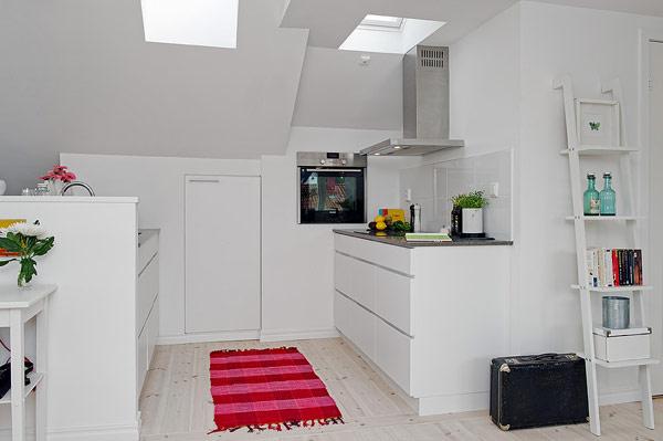 Trên tông nền trắng tinh khôi, chiếc thảm đỏ là điểm nhấn nổi bật nhất cho không gian bếp.