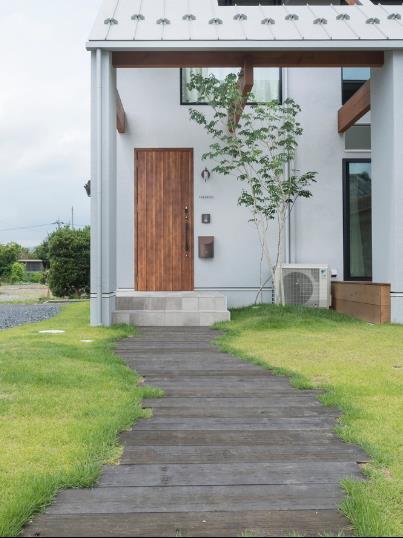 Lối vào nhà quanh co với hai bên là cỏ xanh mơn mởn.