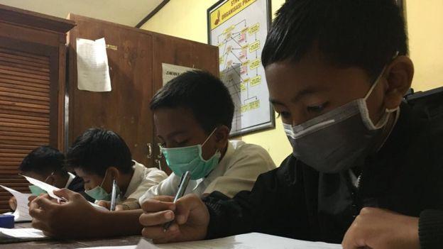 Học sinh ở gần khu vực núi Agung phải đeo khẩu trang để tránh hít phải khói bụi độc từ núi lửa. Ảnh: BBC.