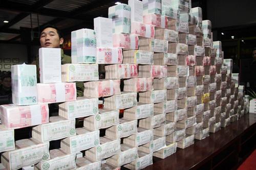 Những cọc tiền mới cứng được xếp thành bức tường dài trên sân khấu.