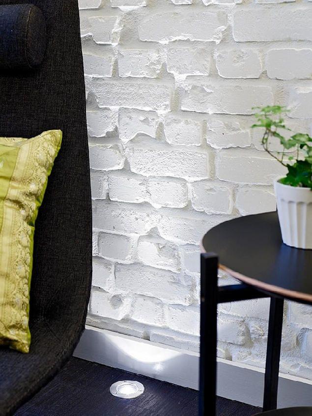 Sự thô mộc của tường gạch cộng với ánh sáng điện hắt lên từ sàn nhà còn giúp tăng thêm nét quyến rũ, khoáng đạt cho không gian bé nhỏ này.