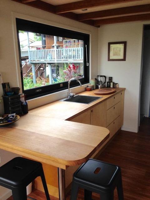 Đối diện phòng khách là không gian bếp. Khu vực này được khéo léo phân làm hai bên một bên là chậu rửa cùng bàn ăn, bên kia là góc nấu nướng với hệ thống tủ kệ dùng cho nhà bếp.