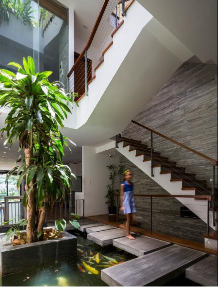 Chân cầu thang tầng 1 còn có một bể cá lớn vừa là điểm nhấn bắt mắt vừa giúp điều hòa không khí làm mát cho ngôi nhà.