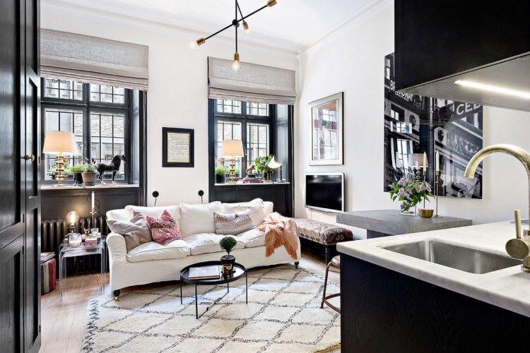 Bộ Sofa trắng nhỏ xinh với kiểu dáng đơn giản kê sát cửa sổ kính rộng, nhờ đó vẫn đủ chỗ cho một chiếc bàn nhỏ để những vật dụng trang trí hay sách. Có cả nơi để 1 chiếc ghế băng dài và góc treo tivi.