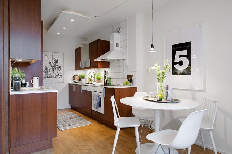 Góc bếp nấu gọn gàng và ấm ấp với nội thất gỗ. Toàn bộ sàn nhà được lát gỗ trải dài từ hành lang cho đến phòng khách rồi kéo vào bếp, tạo nên sự đồng nhất cho căn hộ.