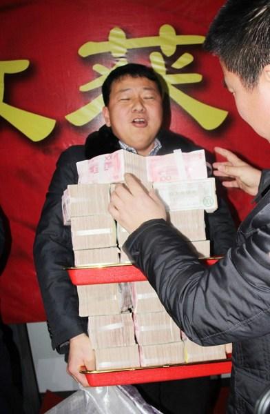 Một nhân viên khệ nệ bê chồng tiền thưởng với nhiều cọc tiền