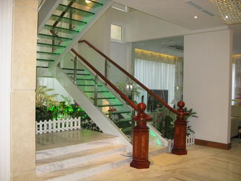 Hiện nay, kiểu cầu thang bằng kính cường lực còn được kết hợp sử dụng kèm theo một số phụ kiện khác như tay vịn gỗ, trụ nhôm giúp không gian trở nên nổi bật hơn.
