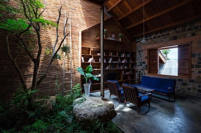 Khu vực phòng khách với sofa gỗ kiểu xưa nhưng lại khéo léo kéo sự hiện đại đến bằng lớp đệm xanh navy cá tính.
