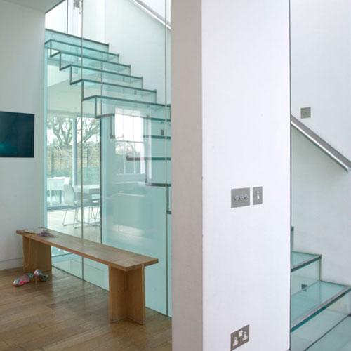 Cầu thang kính kết hợp lan can cùng tông giúp không gian trở nên sáng sủa, sang trọng và hiện đại.