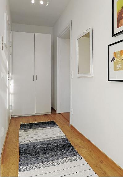 Lối vào nhà nhỏ xinh được nhấn nhá với những bức tranh treo tường bắt mắt cùng tấm thảm lớn.