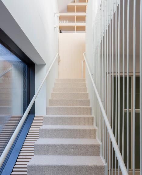 Lối đi lên tầng được thiết kế với bậc cầu thang gỗ và tay vịn bằng sắt sơn trắng.