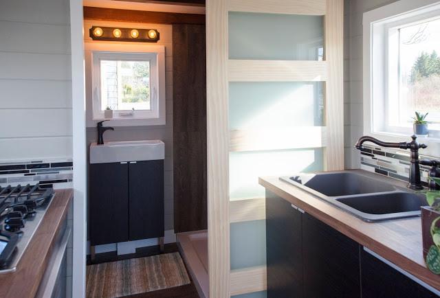 Bồn rửa thoáng sáng nhờ một cửa sổ kính lớn ngay bên cạnh. Góc bếp nhỏ còn được trưng bày những chậu cây cảnh mang màu xanh tươi mát cho không gian.