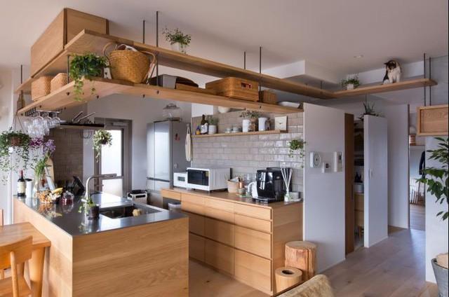 """Góc nấu nướng được đặt gọn trong hệ thống bar quây bằng gỗ đầy ấn tượng. Mọi tủ đựng đồ, kệ hay bếp nấu được """"giấu"""" gọn gàng bên trong khu vực nho nhỏ này."""