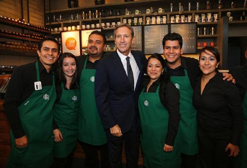 Giám đốc điều hành Starbucks ông Howard Schultz (giữa) và nhân viên cùng chụp ảnh.