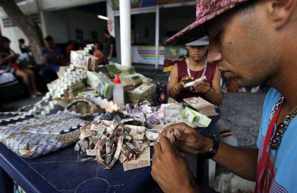 Lạm phát leo thang, người dân Venezuela dùng tiền để gấp đồ thủ công đem bán - Ảnh 1.