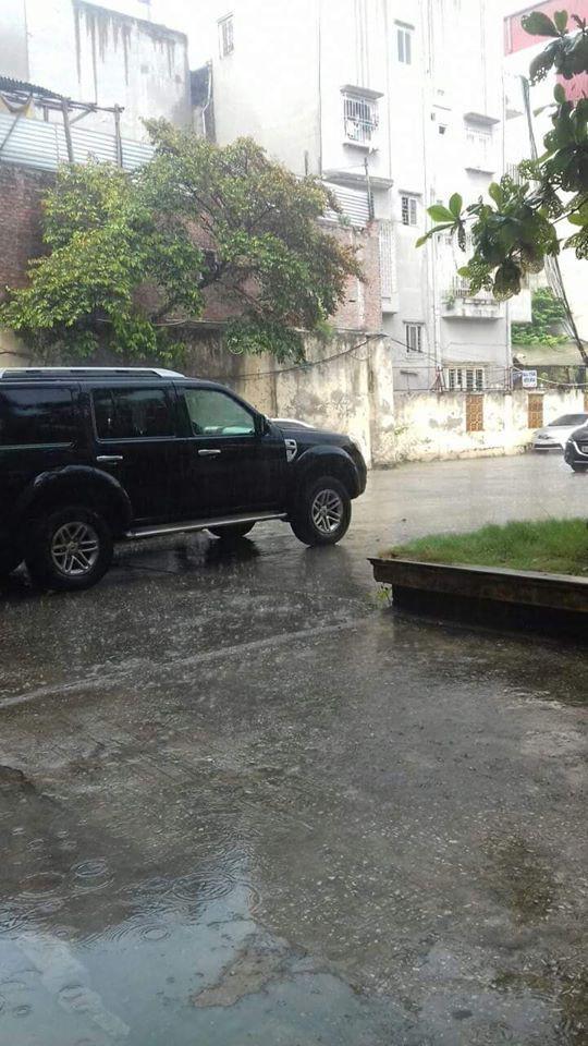 Người Hà Nội đứng giữa đường đón mưa vàng sau nhiều ngày nóng 40 độ C - Ảnh 2.