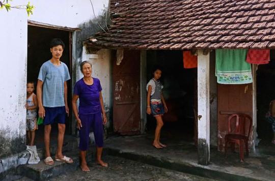 Bà Nguyễn Thị Chớn bên căn nhà đã xuống cấp mà không rút được tiền để sửa chữa