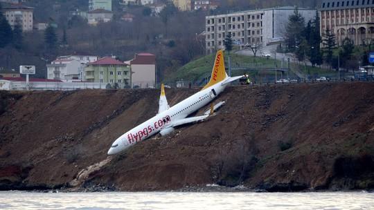 """Máy bay chở 160 người trượt khỏi đường băng, """"treo"""" trên vách đá - Ảnh 1."""