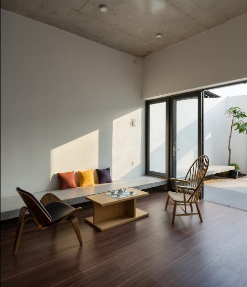 Góc tiếp khách được thiết kế đặc biệt đơn giản với chiếc bàn café thấp, ghế tiếp khách là băng ghế dài bằng bê tông xuyên suốt chiều dọc bức tường vô cùng thuận tiện. Bên cạnh còn có một chiếc ghế mây và ghế bành lạ mắt.