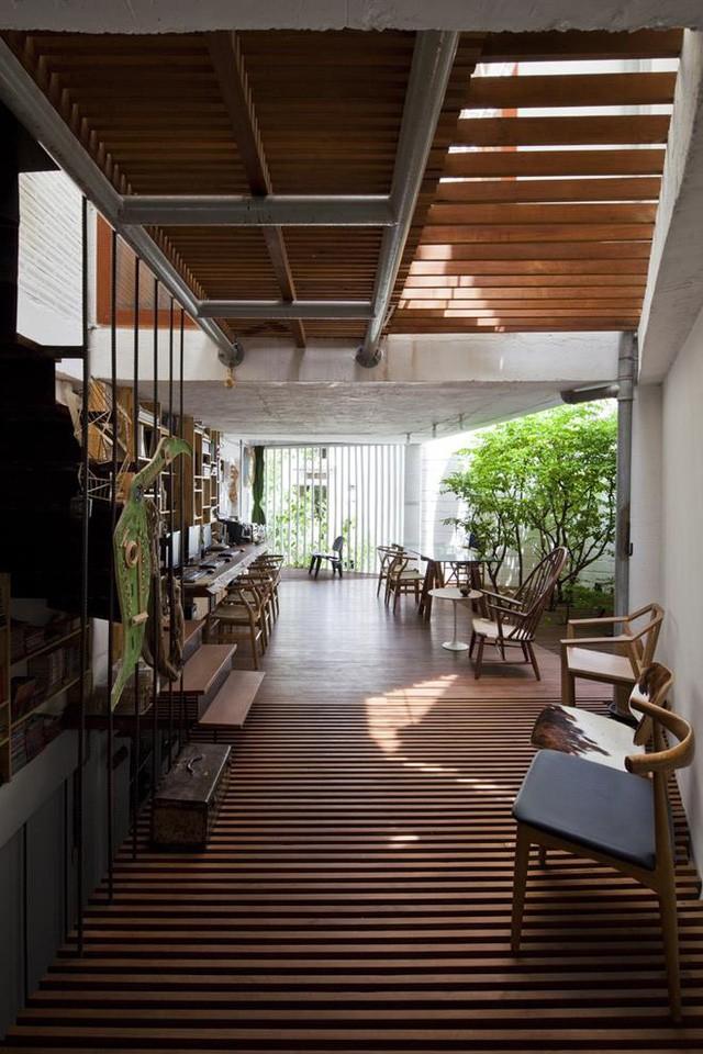 Ngay bên cạnh là không gian làm việc và giá đựng sổ sách tài liệu. Một mảng tường nhà được thiết kế với những thanh lam dọc thay cho bức tường kín giúp không gian ngôi nhà vô cùng rộng thoáng.